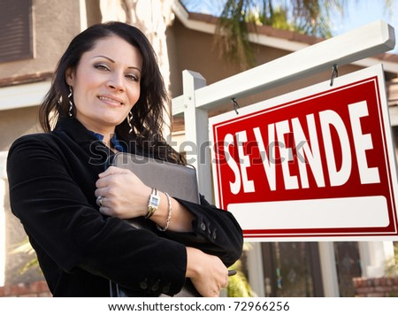 Proud, Attractive Hispanic Female Agent In Front of Spanish Se Vende Real Estate Sign and House.