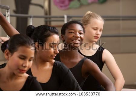 Proud ballet student with peers in a dance studio