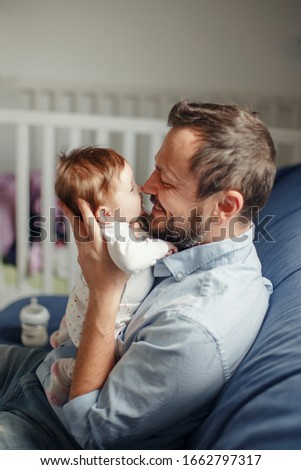 Proud Caucasian father talking to newborn baby girl. Parent holding rocking child daughter in hands. Authentic lifestyle happy parenting fatherhood moment. Single dad family home life. Foto d'archivio ©