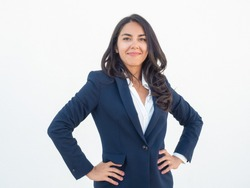Proud confident business woman posing over white background. Happy beautiful young Latin woman in office suit placing hands on hip, looking at camera and smiling. Business success concept