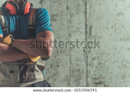 Proud Construction Worker Closeup on the Raw Concrete Wall. Caucasian Contractor. #1055906591