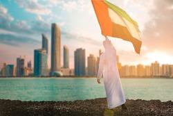 Proud Emitrati Young Man rising UAE flag celebrating National day in Abudhabi