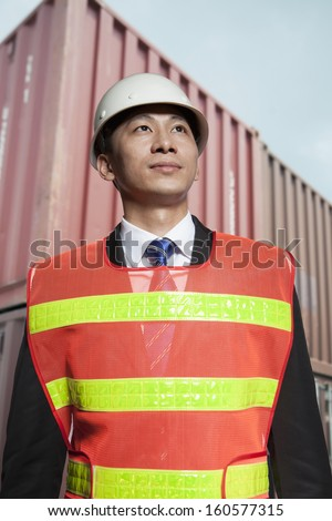Proud engineer in protective work wear standing in shipping yard
