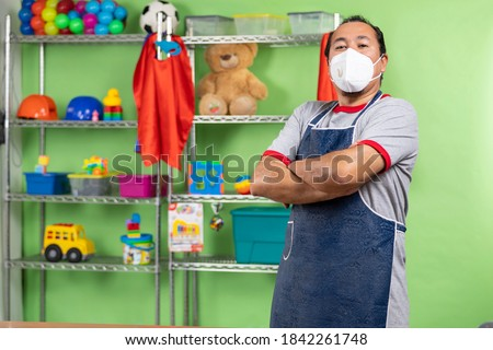 Proud enterprising man with a mask, during a COVID-19 pandemic, in his toy store,attending and showing his toy store. looking at the camera