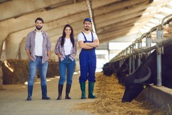 Proud farmer and happy farm workers at work. Portrait of smiling young people looking at camera standing in livestock barn with feeding black cows and buffalo. Animal husbandry and cattle farming jobs