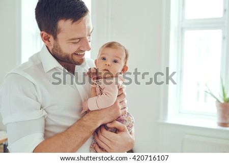 Proud father holding his newborn baby daughter in his at home