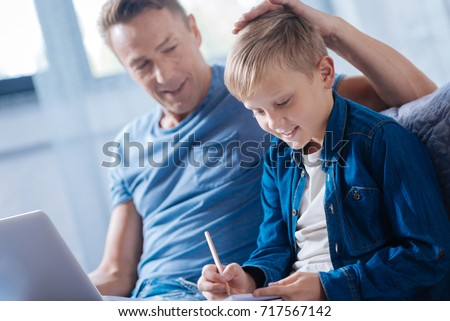 Proud father patting son on the head while he studying