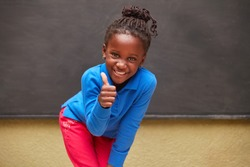 Proud girl as elementary student stands in front of a blackboard with thumb up