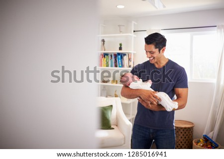 Proud Hispanic father holding his four month old child at home, seen from doorway #1285016941