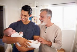 Proud Hispanic father holding his four month old son at home, grandfather standing beside them