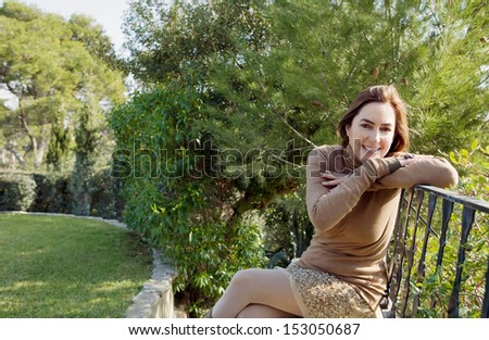 Proud home owner middle aged attractive woman sitting on her home garden bench and leaning on a banister during a sunny autumn fall season day, outdoors.