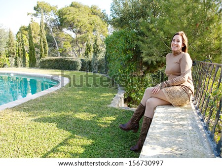 Proud home owner relaxing in her country home garden with trees and a swimming pool during a sunny autumn morning, sitting on a stone wall with veranda balcony.
