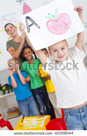 proud kindergarten boy holding painting high