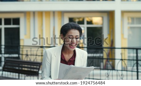Proud mixed race business woman examining documents at urban street. Close up smiling businesswoman screening finance data outdoors. Mixed race female entrepreneur celebrating victory outside ストックフォト ©