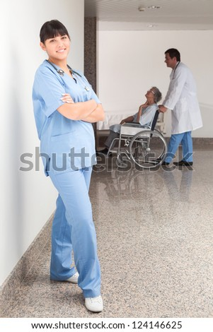 Proud nurse standing in hospital corridor