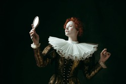 Proud of her self. Medieval redhead young woman in golden vintage clothing as a duchess looking in the mirror on dark green background. Concept of comparison of eras, modernity and renaissance.