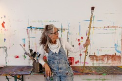 proud older artist woman, in her fifties with grey hair and black glasses holds a very big paintbrush