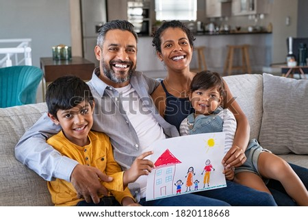 Proud parents showing family painting of son and daughter sitting on sofa at home. Smiling african mother and middle eastern father with two children looking at camera. Brothers showing painting.
