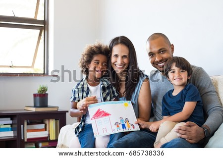 Proud parents showing family painting of son sitting on sofa at home. Smiling mother and father with children?. Black boy with his family at home showing a painting of a happy multiethnic family.