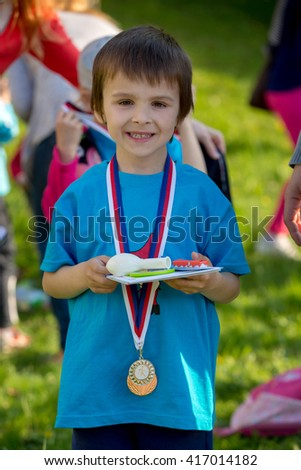 proud preschool boy holding prizes and medals after annual sport kinder garden competition 417014182 - Kinder Kid Competition
