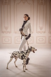 Proud, strong, stylish, girl hunter, in costume riding woman posing with a Dalmatian dog. The background is classic sofa, walls with moldings. makeup smokey eyes, strict, creative hairstyle bagels.