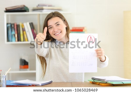 Proud student showing approved exam to camera at home