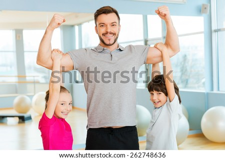 Proud to be strong. Cheerful young sporty father showing his biceps while children bonding to him and smiling