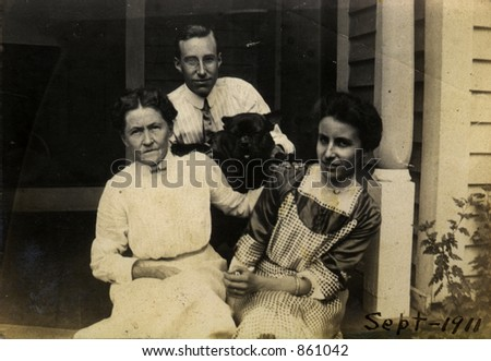 Proud vintage mother with her adult children and the family pet.  Original Circa 1911 print has scratches, stains, artifacts, fading and solarization qualities.