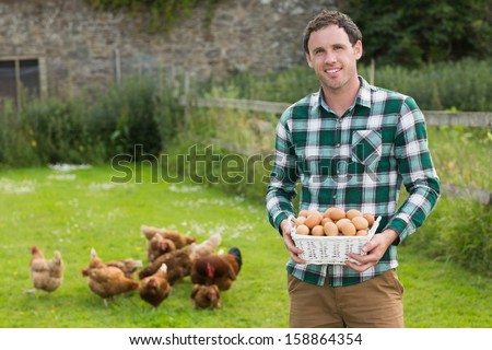 Proud young man holding a basket filled with eggs with chickens behind him