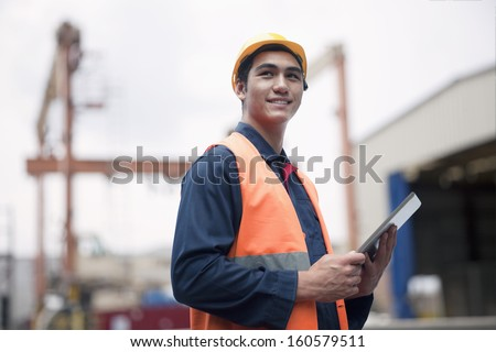 Proud young worker in protective work wear in shipping yard