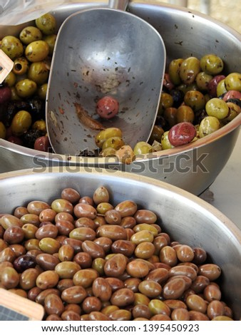 Provencal olive mix in silver metal bowls and scoop at farmers' food market in Occitanie, southwestern France. Vertical closeup , selective focus of marinated green and dark olives #1395450923
