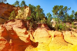 Provence, France. Bizarre, brightly colored rocks lit by the midday sun. Walk along the most beautiful red-yellow-orange route. The rocks are covered with forest. The village of Roussillon