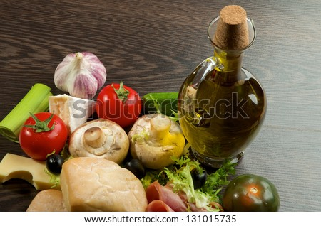 Provence Still Life with Vegetables, Hamon, Ciabatta, Cheese and Olive Oil closeup on Dark Wood background