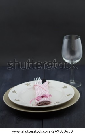 Provence table setting: plate, fork, knife, pink napkin, glass on dark wooden table