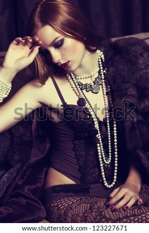 Provocative Sophisticated Redhead Young Woman in Black Lingerie and Beads posing - stock photo