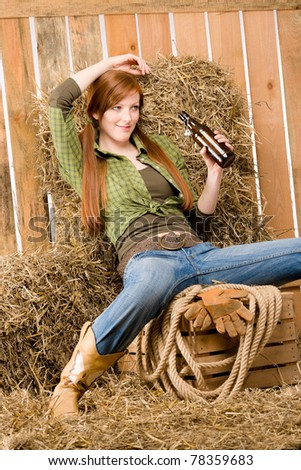 Provocative young cowgirl drink beer in barn country style