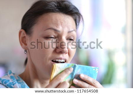 prstuzhennaya young woman sneezing into a handkerchief