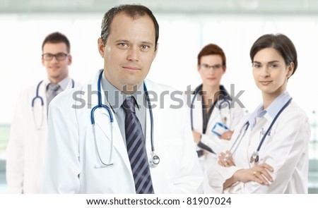 Prtrait of mid-adult doctor leading medical team, smiling.?
