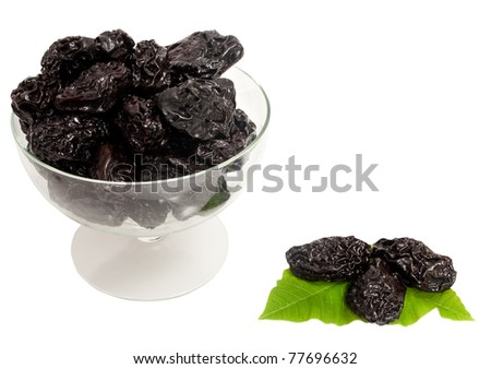 prunes in a glass bowl with green leaves isolated on white background
