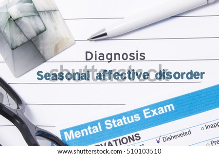 Psychiatric Diagnosis Seasonal Affective Disorder. Medical book or form with name of diagnosis Seasonal Affective Disorder is on table of doctor surrounded by questionnaire to determine mental state