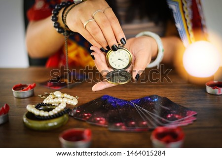 Psychic readings and clairvoyance concept / Crystal ball fortune teller with hands hold retro pocket watch and Tarot cards reading divination , Magic Spiritual and Horoscopes