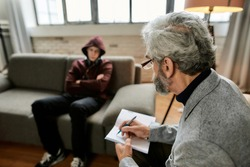 Psychoanalyst taking notes in notepad during appointment with uneasy teenage boy sitting with crossed hands on couch in office. Psychotherapy concept