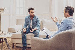 Psychological treatment. Professional handsome psychologist helping his patient while having a session with him
