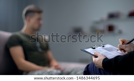 Psychologist making notes during therapy session with sad male soldier, PTSD