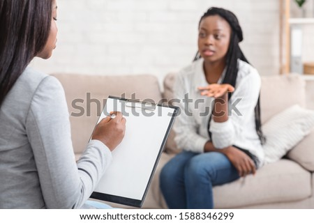 Psychologist taking notes during therapy session with her emotional female patient that talking with about her problems and actively gesturing