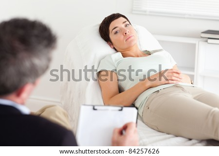 Psychologist talking to a depressed female patient in a room