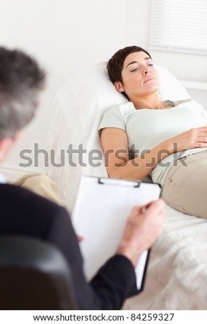 Psychologist talking to a female patient in a room