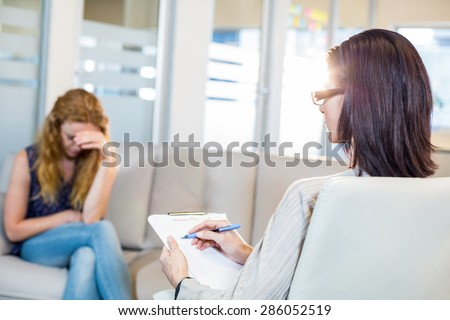 Psychologist talking with her depressed patient and taking notes in the office