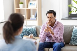 psychology, mental therapy and people concept - sad young indian man patient with glass of water and woman psychologist at psychotherapy session