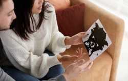 Psychology Test. Couple Holding Inkblot Picture Discussing It During Marital Therapy Session Sitting In Psychologist's Office. Cropped, Selective Focus